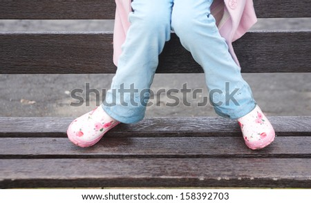 Front view of a young girl legs wearing blue trousers and pink wellington boots, sitting on the edge of a wooden bench in a park during a rainy wintry day, outdoors. - stock photo