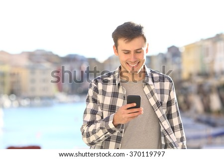 Front view of a young handsome man walking towards camera and using a smart phone on line outdoors in summer - stock photo