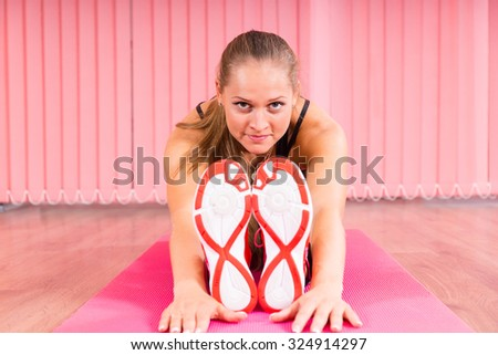 Front View of an Athletic Young Woman Stretching her Arms and Legs on Top of a Fitness Mat Inside the Studio. - stock photo