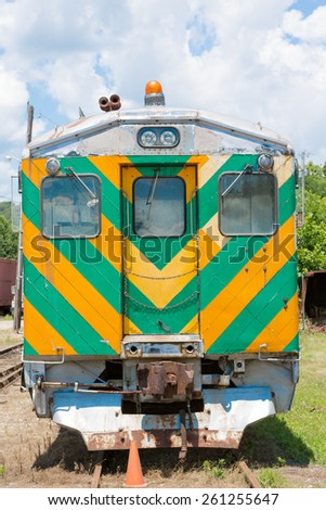 Front view of an old train or railroad rolling stock parked in a siding with colorful green and yellow warning chevron, emergency light and door in a transport and travel concept - stock photo