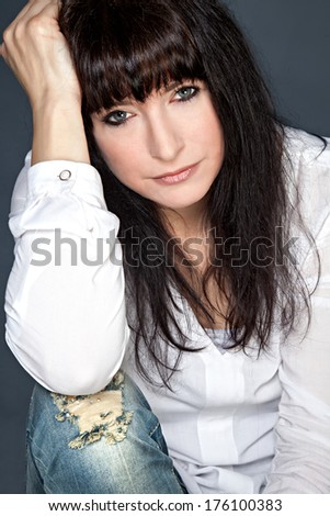 Front view of attractive brunette woman looking into the camera - stock photo