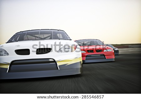 Front view of auto racing race cars racing on a track with motion blur.  - stock photo