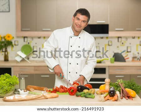 front view of caucasian man wearing chef clothing, cutting vegetables in kitchen, smiling - stock photo