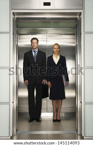 Front view of confident businessman and businesswoman standing together in elevator - stock photo