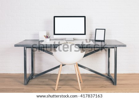 Front view of designer desk with blank white computer screen, frames and other items with white chair next to it. Wooden floor and white brick wall background. Mock up - stock photo