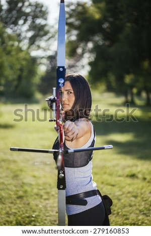 Front View Of Female Archer Training At The Range - stock photo