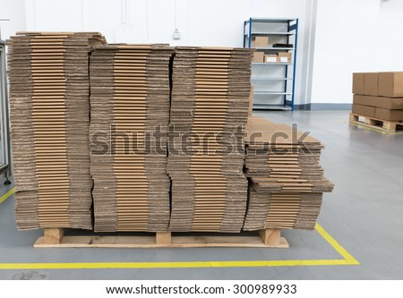 Front view of folded cardboard boxes are made up in a designated place in the assembly hall. All potential trademarks are removed. - stock photo