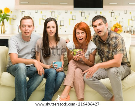 front view of four caucasian people sitting on sofa watching movie and acting amazed - stock photo