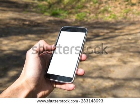 Front view of hand holding black smartphone with white blank screen in forest. - stock photo