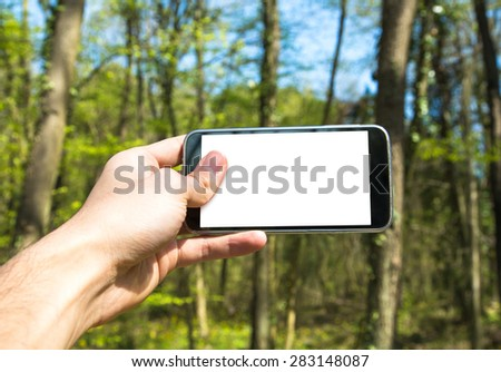Front view of hand holding horizontal black smartphone with white blank screen among trees. - stock photo