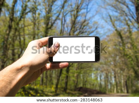 Front view of hand holding horizontal black smartphone with white blank screen in forest. - stock photo
