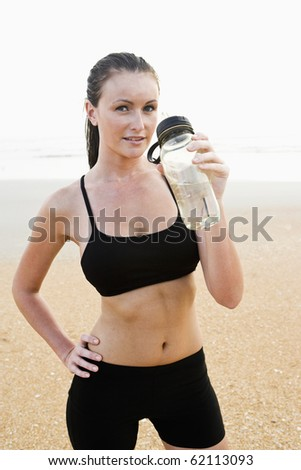 Front view of healthy fit young woman on beach drinking water - stock photo