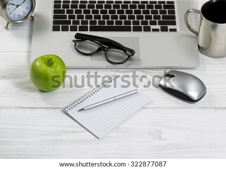 Front view of laptop computer with office work objects and coffee. Layout in horizontal format. - stock photo