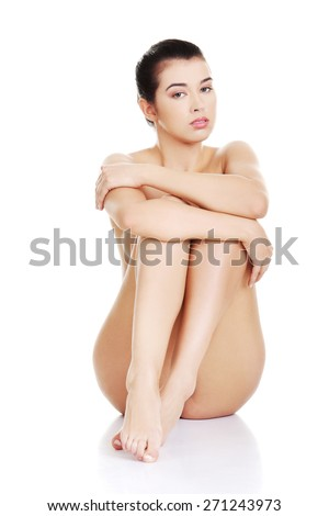 Front view of nude woman sitting on the floor. - stock photo