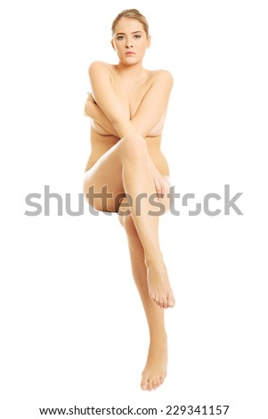 Front view of nude woman sitting with cross legs on something invisible. - stock photo