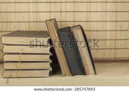 Front view of old books stacked on a shelf. Books without title and author. - stock photo