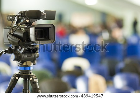 Front View of Professional Videocamera. Positioned Against Blurred Background. Horizontal Image - stock photo