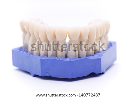 Front view of prosthetic teeth organized on a blue support base isolated on white background - stock photo
