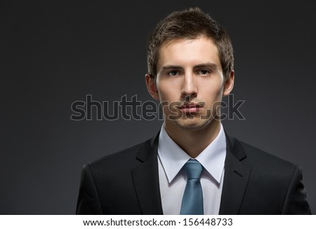 Front view of self-confident business man in dark suit with black tie. Concept of professionalism and success in business - stock photo