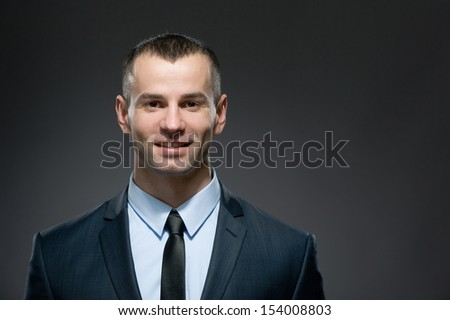 Front view of self-confident man in dark suit with black tie. Concept of professionalism and success in business - stock photo