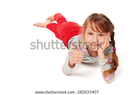 Front view of smiling child girl lying on stomach on the floor gesturing thumb up, over white background  - stock photo