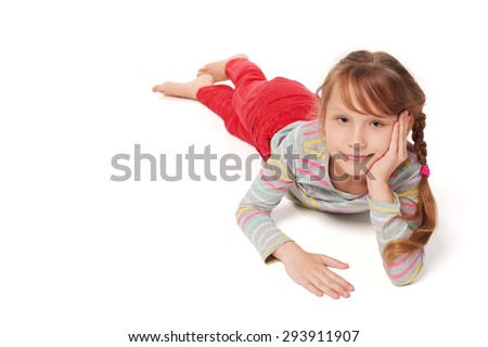 Front view of smiling child girl lying on stomach on the floor looking at camera smiling, over white background  - stock photo