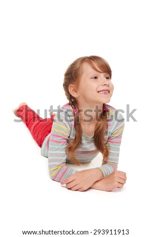 Front view of smiling child girl lying on stomach on the floor looking away at blank copy space, over white background  - stock photo