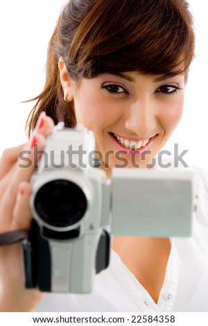front view of smiling female holding video camera on an isolated white background - stock photo
