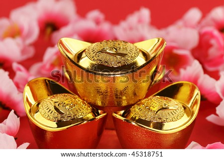 Front view of some chinese gold ingots surrounded by cherry blossoms on a red background - stock photo