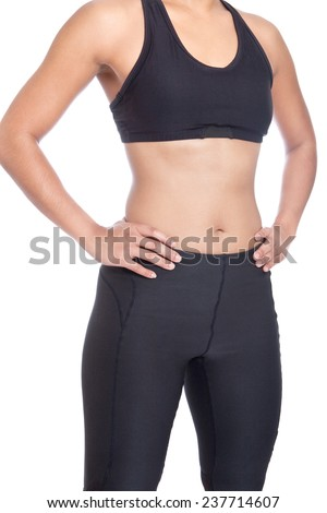 Front view of sport woman in black exercise attire with sport bra and lycra pants with hands on hip. - stock photo