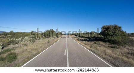 Front view of Straight road with blue sky - stock photo