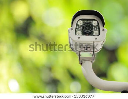 front view of surveillance camera or cctv against nature background - stock photo