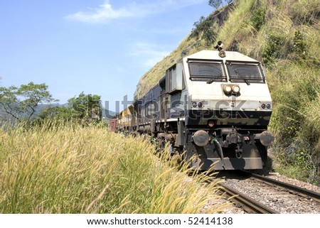front view of the engine of a train passing by the middle of a landscape - stock photo