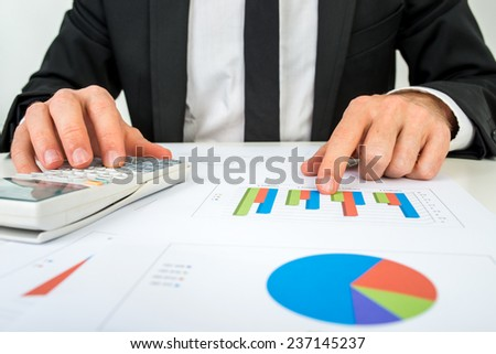 Front view of the hands of a accountant analysing a bar graph using a manual calculator to check the statistics and projections. - stock photo