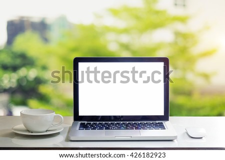 Front view of the laptop and coffee cup is on the work table in office window - stock photo