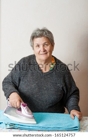 Front view of the senior women iron clothes, indoor shot - stock photo