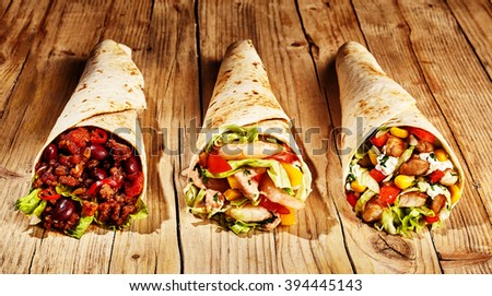 Front view of three meat, bean and vegetable burritos in wheat tortillas on old wooden table table - stock photo