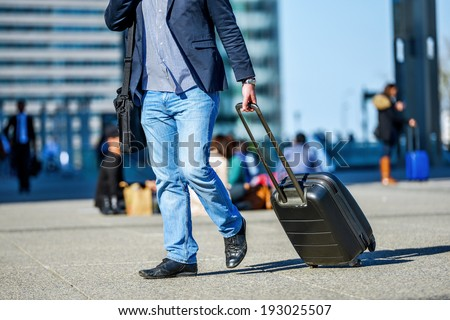 front view of traveler man walking with suitcase in the street - stock photo