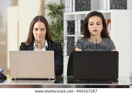 Front view of two angry businesswomen looking each other with hate working with laptops at office - stock photo