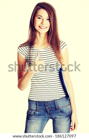 Front view portrait of a young happy female caucasian student holding a notebook and giving a thumb-up - stock photo