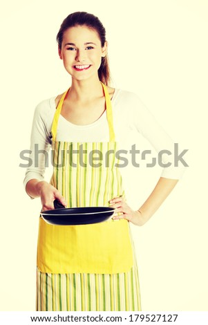 Front view portrait of a young smiling caucasian female teen dressed in apron, holding a frying pan in front of her, on white. - stock photo