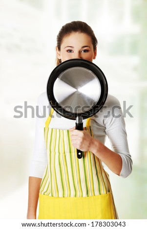 Front view portrait of a young smiling caucasian female teen dressed in apron, smiling behind the frying pan. - stock photo