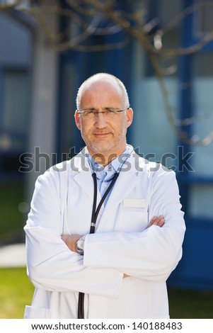 Front view portrait of confident male doctor standing with arms crossed - stock photo
