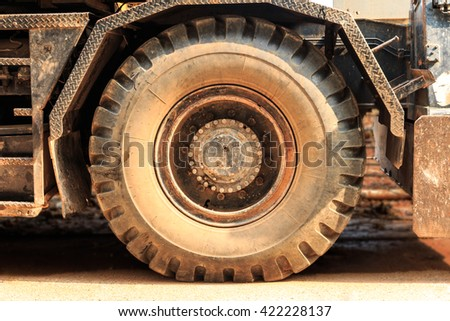 Front view tractor wheels tire in the dust. - stock photo