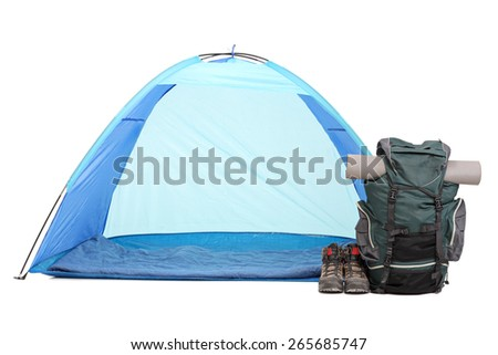 Frontal shot of blue tent, a rucksack with hiking equipment and a pair of boots isolated on white background - stock photo