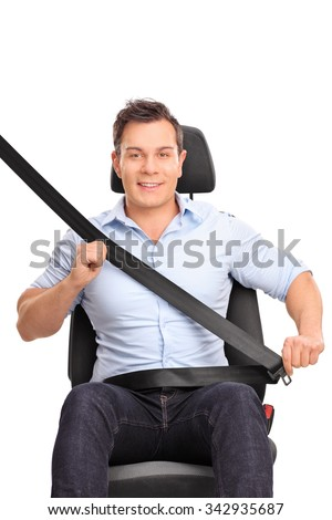 Frontal vertical shot of a young man sitting on a car seat and fastening his seat belt isolated on white background - stock photo