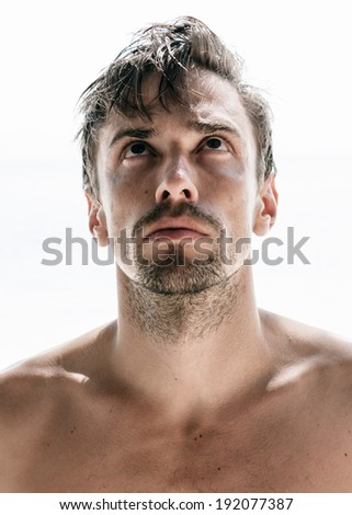 Frontal view of the portrait of a young caucasian handsome man, shirtless and unshaven, with rebel hair, looking up, on white background - stock photo