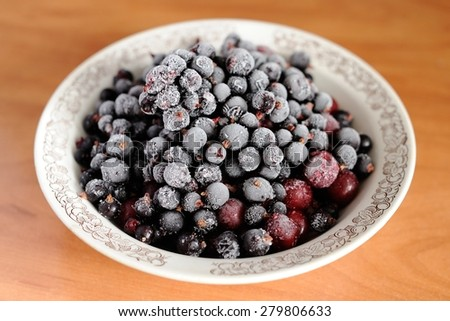 Frosen black currant and cranberry berries in white bowl - stock photo