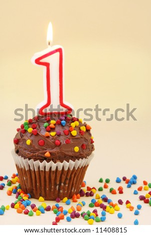 Frosted chocolate cupcake with a numeral one candle.  Surrounded by colourful sprinkles. - stock photo
