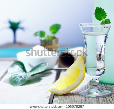 Frosted garnished vodka in a shot glass with a slice of fresh tangy lemon chaser served on a wooden deck alongside the sea at a tropical resort - stock photo